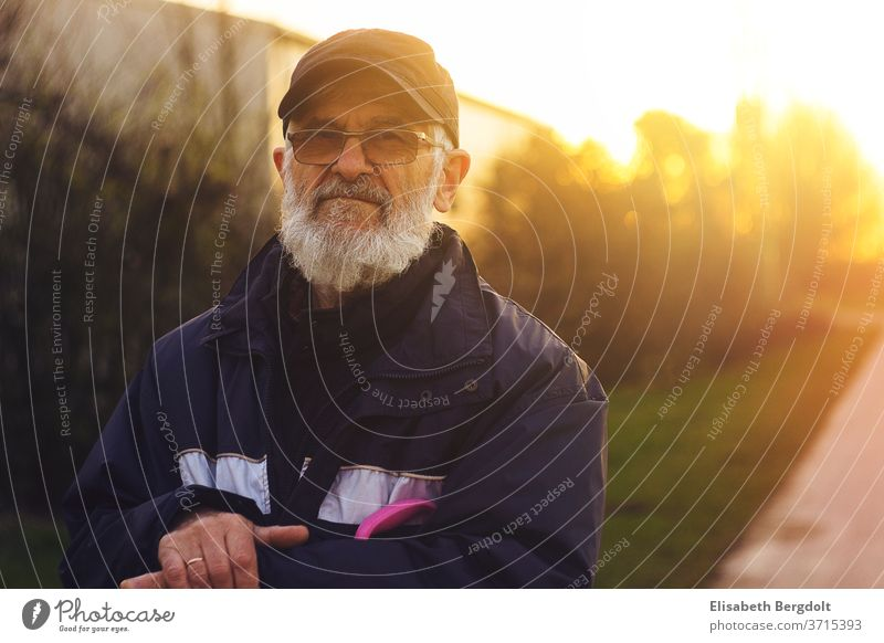 Portrait of a 75 years old man with glasses and beard, outside, at sunset Man older man Eyeglasses portrait Facial hair Sunset Senior citizen To go for a walk