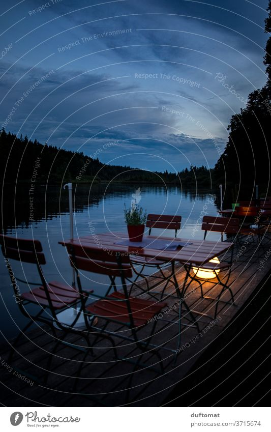 Table for four at the lake in the evening mood Lake Beer garden Idyll reflection Water Nature Reflection feed sb./sth. Blue Calm Sky Clouds Sunset Evening out