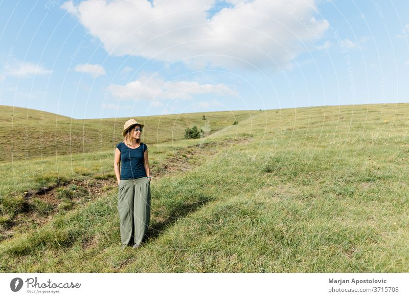 Young woman enjoying on the hillside meadows adult carefree casual caucasian cheerful countryside environment explore female field freedom grass green happiness