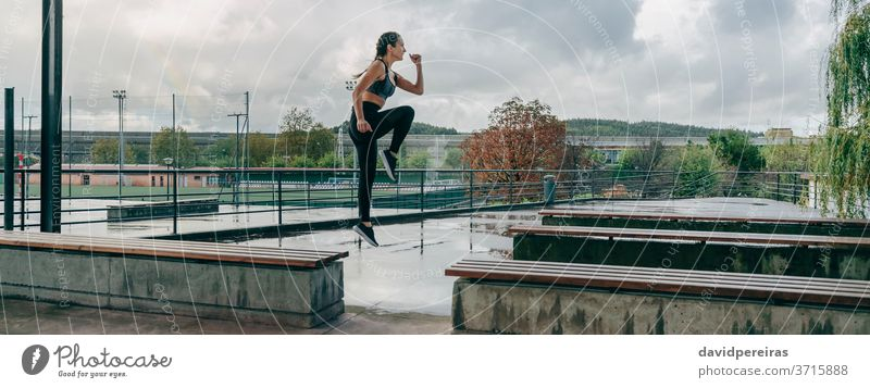 Girl jumping on benches doing training rainy sport girl energy empowerment style body boxer braids fitness banner web panoramic panorama health healthy exercise