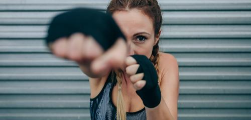 Sportswoman looking at camera and punching sportswoman strong looking camera hitting boxing bandage empowerment metal wall training boxer braids fitness body