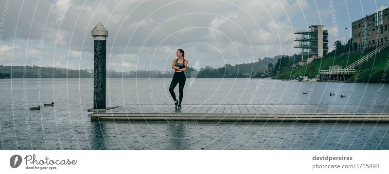Sportswoman looking lake from pier rain sportswoman posing crossed arms serenity boxer braids fitness workout raining brave banner web panoramic panorama