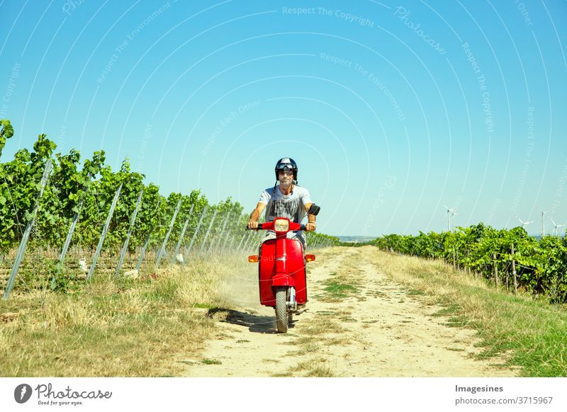 Riding a scooter in the vineyard. Man, with helmet riding scooter in the countryside. Portrait of a man and with a stylish vintage moped in summer against a blue sky