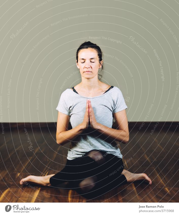 Woman sitting cross-legged on the floor doing yoga relaxation exercises. Concept of healthy living and yoga exercising people meditating women flexibility