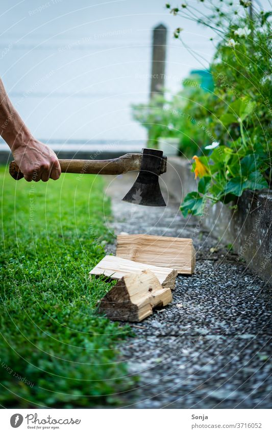 Man chops wood with an axe in the garden. Section. Axe Firewood Chop Garden Grass green out Exterior shot Nature Stack of wood by hand over40 Day Fuel Detail