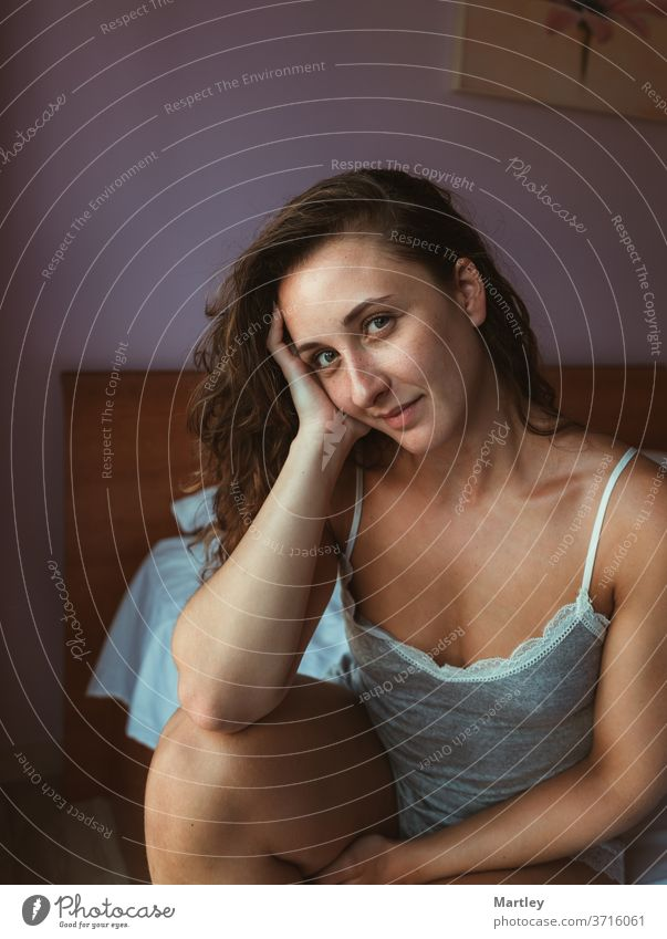 Pleased female in nightwear rumpling hair and looking at the camera while sitting on soft bed in morning woman bedroom indoors relaxation dreaming pillow sexy