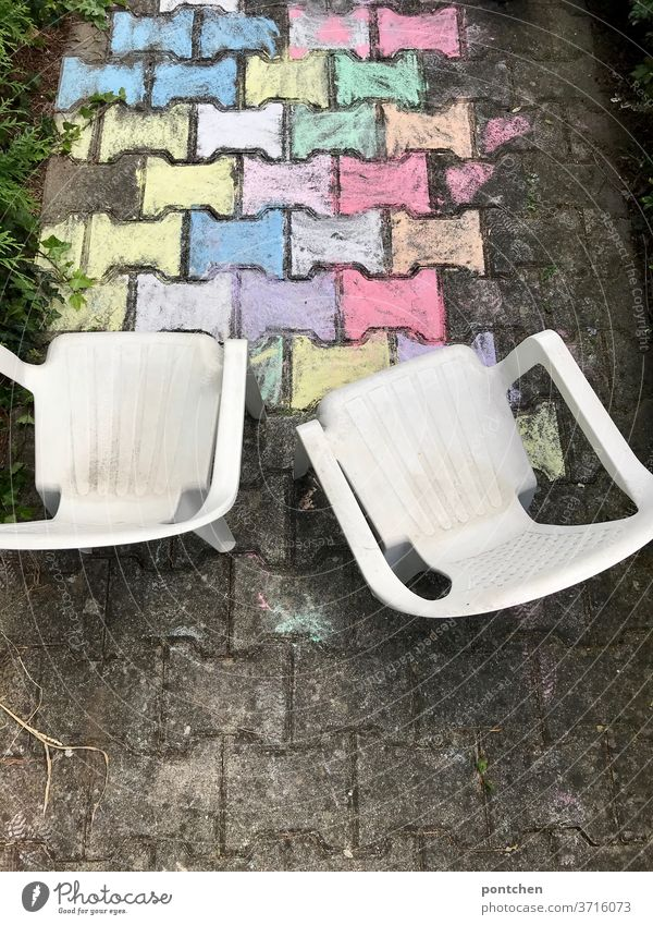 Two plastic garden chairs for children stand in front of a colourful painting in street chalk. Child's play Garden chairs Children's game Street painting