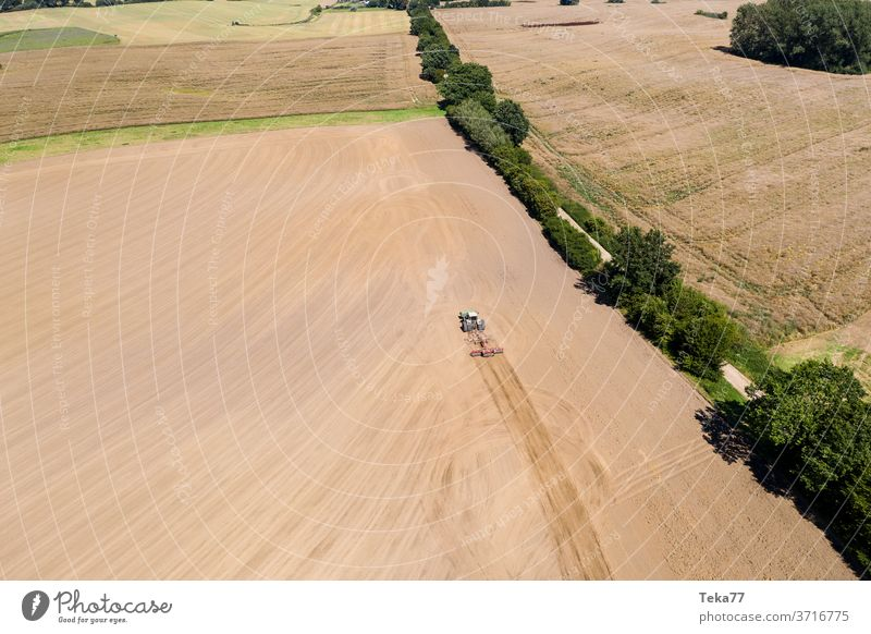 a tractor in a farming landscape with a plow from above tractor from above tractor with a plow field meadow dry nature earth dry earth crop mud eco farming