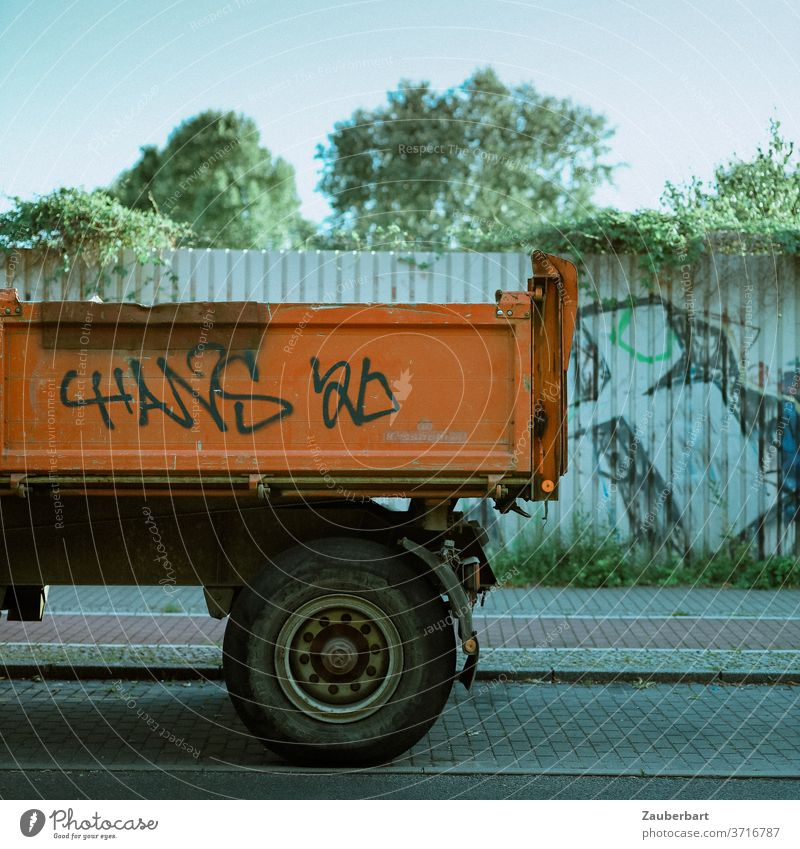 Loading area of a truck in orange in front of a sheet metal wall lorry lorries Vice Orange Loading space Wheels Tire Wall (building) Tin Fence graffiti Street