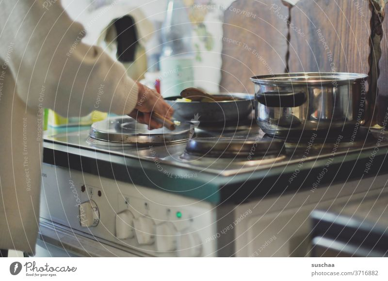 elderly woman stands at the stove and prepares a meal Woman Old Stove Stand boil Eating Cooking Prepare Hotplate saucepan Pan Cutting boards cake