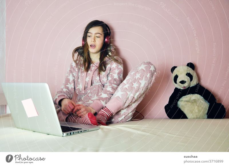 teenagers sit in front of their laptops and listen to music or chat with friends. the panda stuffed animal is also there ... youthful Youth (Young adults) Child