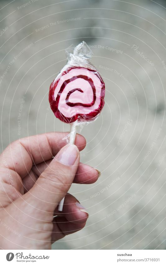 hand holding a lollipop by hand Fingers Woman Sugar Sweet Candy Food Delicious Lollipop Cavities Unhealthy Spiral Tasty Red White