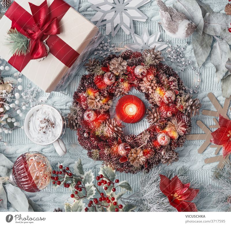 Christmas concept: advent wreath, present, hot chocolate in mug, Christmas flower, snowflakes, Christmas balls, and holly on light blue textile background. Top view