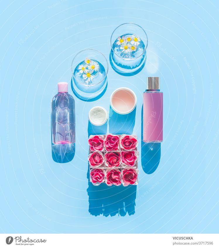 Composition of natural cosmetic products and glasses with daisies, bottles, tubes and flowers on light blue background. Summer skin care concept. Top view . Spa or wellness
