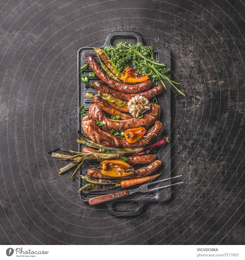 Grilled sausages on cast iron plate. Top view griddle grilled food pepper spring onion garlic paprika herbs carrot meet fork summer barbecue concept dark table