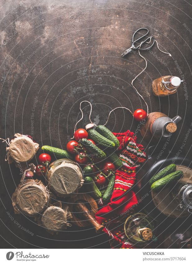Preparation of homemade pickled cucumbers in jars . Rustic . Border preparation scissors cord red kitchen towel oil vegetables rustic autumn concept dark