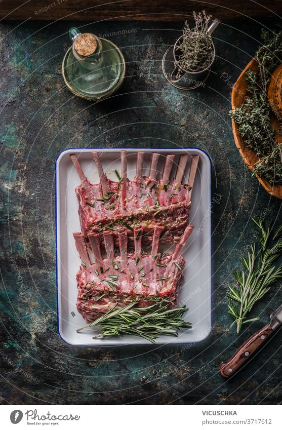 Raw lamb ribs with herbs and seasonings on a dark rustic kitchen background. Top view. raw spices around top view barbecue bbq bone butcher chop cooking cut
