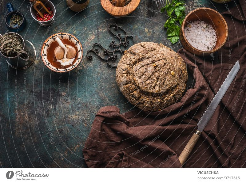 Homemade whole grain bread on dark kitchen table background with knife and cooking tools homemade ingredients top view place text bakery board breakfast brown