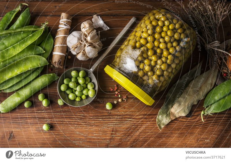Preserving of garden vegetables. Green peas canning in jar on wooden background with ingredients. Top view. Homemade preserve concept green top view healthy