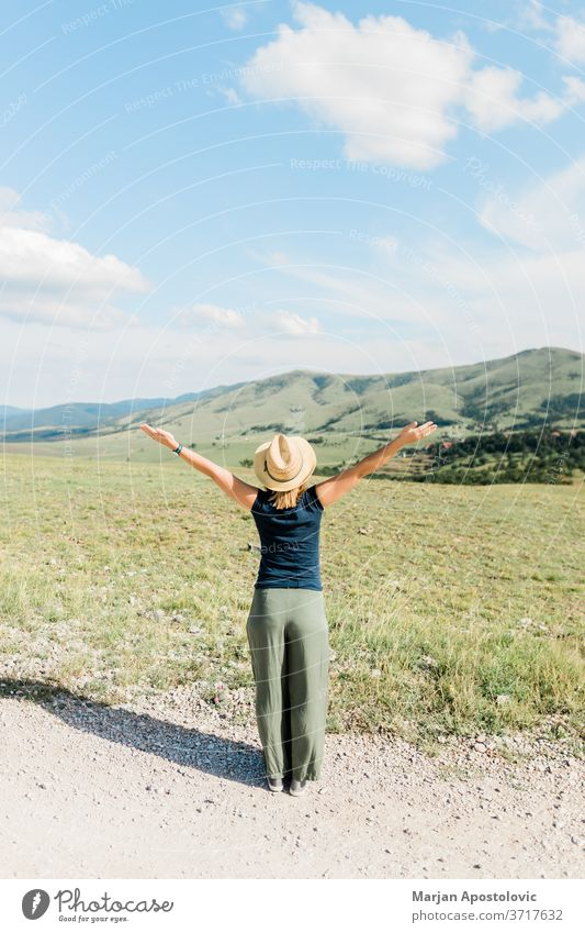 Young female nature lover enjoying the view of a mountain range in summertime adventure arms beautiful carefree casual europe explore freedom girl happiness