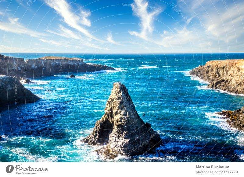 Cone shaped rock in the pacific ocean under a blue sky with clouds, California boulder california landscape travel shoreline beach cone stone water nature