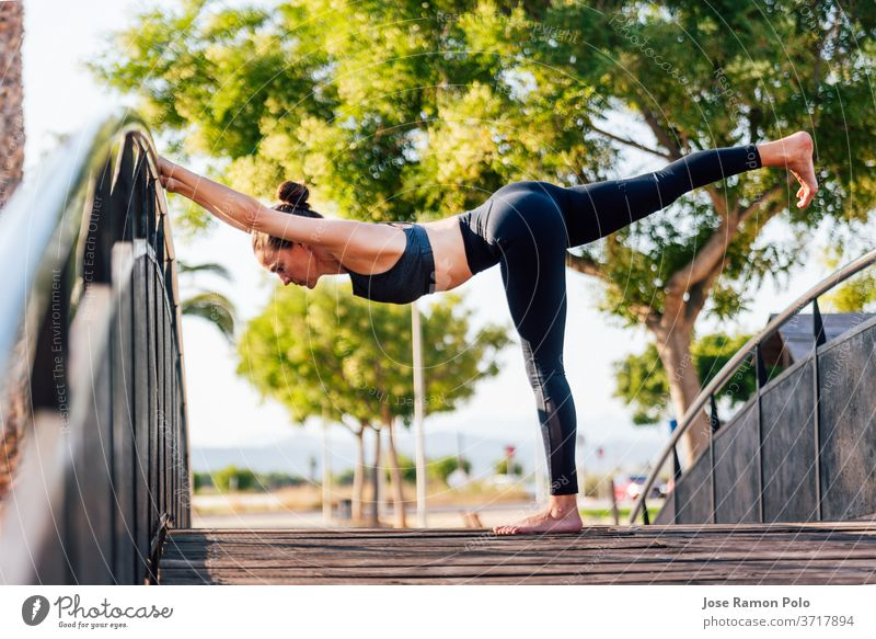 young woman doing exercises on outdoor copper wooden bridge yoga nature fitness health sport pose pretty people balance flexible gymnastic happiness meditation