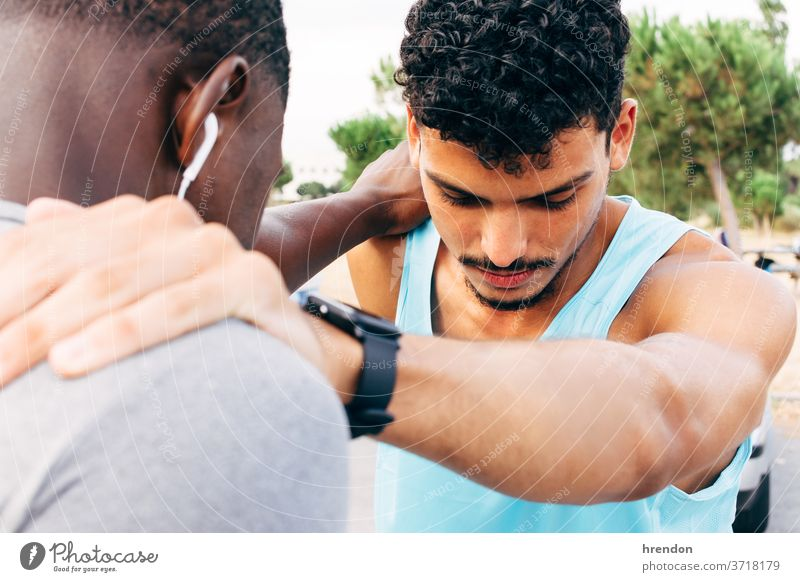 two young men warm up before starting to exercise stretching sport fitness exercising beginnings bonding runner standing together togetherness sunlight