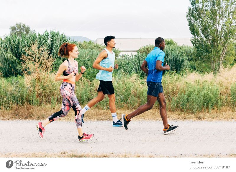 Three friends exercising outdoors, running in rural setting sport three people young men young women athlete vitality motion togetherness friendship female