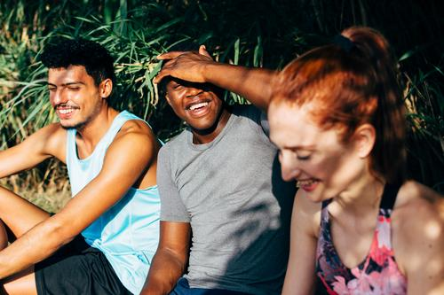 three friends sitting on a bench after exercising outdoors friendship people sport healthy lifestyle togetherness smiling fitness enjoyment happiness talking