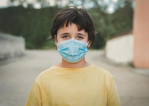 Close-up of kid wearing medical mask coronavirus epidemic pandemic quarantine child covid-19 symptom medicine health positive test hospital city gesture casual