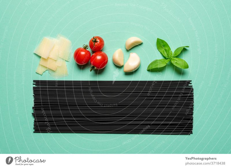 Black spaghetti and sauce ingredients top view. Uncooked pasta isolated on a green background above view aligned basil black black spaghetti carbohydrate carbs