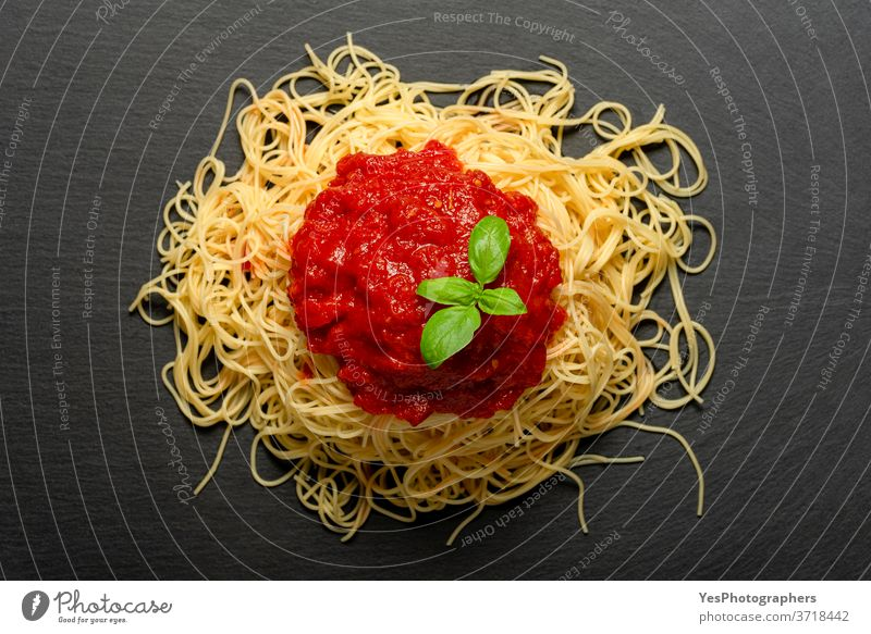 Spaghetti with tomato sauce on a black granite plate. Cooked spaghetti with red sauce. above view background baked basil carbohydrate carbs close-up