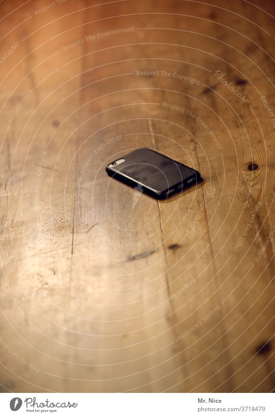 A mobile phone lies on the kitchen table waiting for the next use Telephone Communicate Technology Telecommunications Table Wooden table