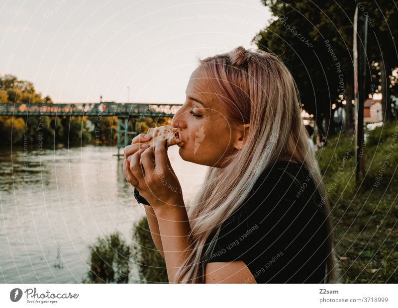 Young woman eating pizza on the banks of the Danube Eating food Fast food Pizza hunger Lunch Food Dinner Nutrition outdoor Regensburg Water Summer vacation