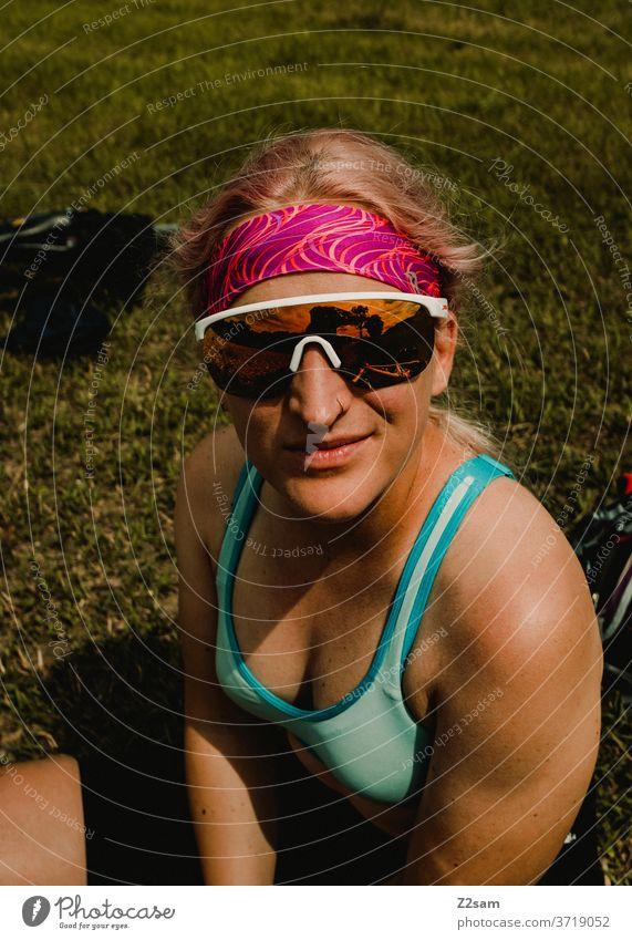 Sporty young woman takes a break Sportsperson sportswoman Young woman girl Top Sportswear sunglasses Headband Brown Skin Body athlete Summer Sun Meadow Blonde