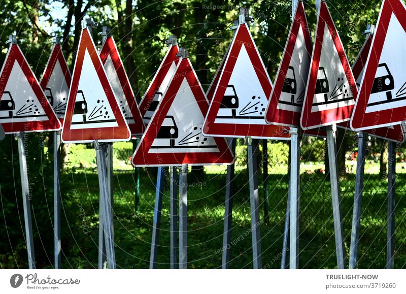 12 identical traffic warning signs, showing a triangle with a thick red border, pointing upwards, on a white background with a black pictogram: a car cut in half, its tyres throwing small stones to the side