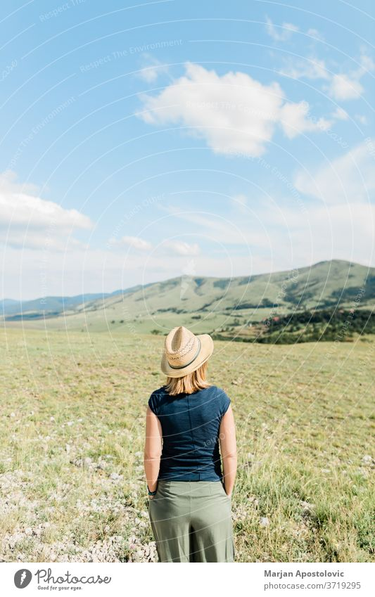 Young female nature lover enjoying the view of a mountain range in summertime adventure beautiful carefree casual europe explore freedom grassland happiness