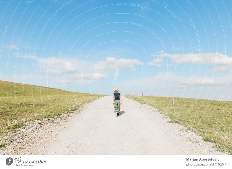 Young female nature explorer walking on a gravel road in summertime adult adventure alone beautiful caucasian challenge countryside dirt environment footpath