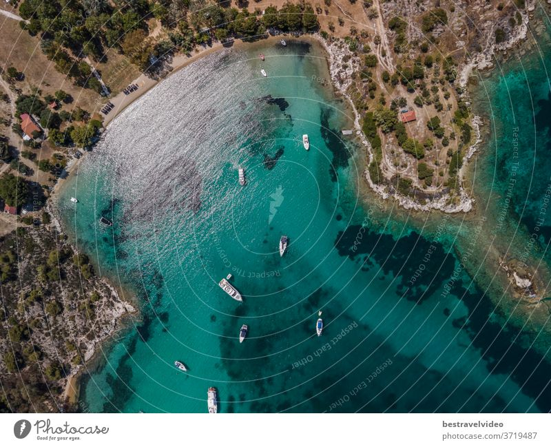 Mediterranean Greek landscape coastal drone shot with moored leisure boats. Aerial day top view of Sithonia Chalkidiki peninsula above shoreline with green plantation and crystal-clear calm sea.