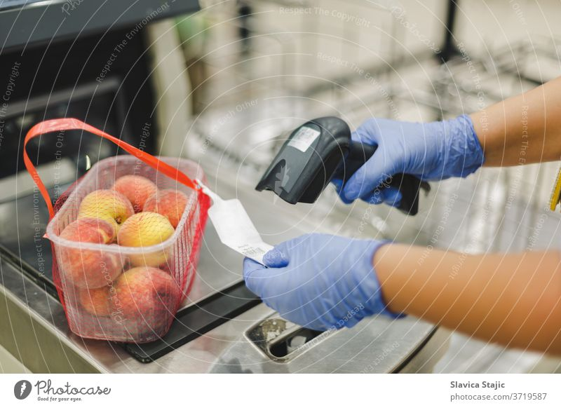 Scanning bar code. Woman or worker in blue medical gloves holding bar code scanner and scanning  paper on peach fruit. Shopping during the corona virus pandemic, selective focus