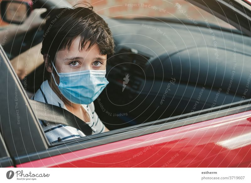 kid wearing medical mask riding in a car coronavirus motor vehicle seatbelts security safety epidemic pandemic quarantine child family covid-19 trip travel