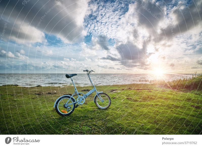 Foldable bike by the ocean at sunset sunny compact sunrise bright pendling scenery summer pedal cycling bicycling outdoors lifestyle blue landscape sea