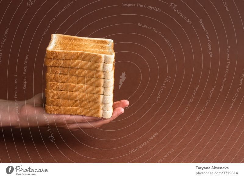 Heap of toasts in hand on brown breakfast bread morning meal food snack toasted white slice baked modern holding