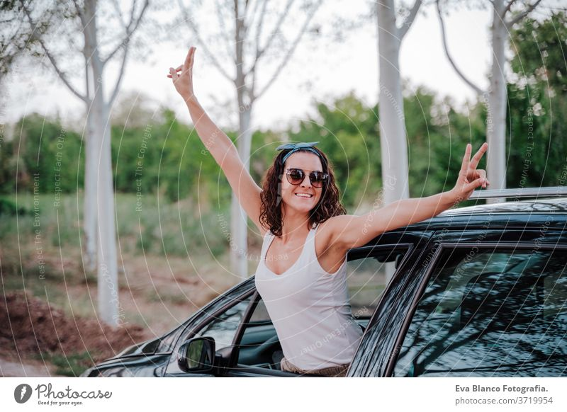 happy young woman in a car. travel and happiness concept outdoors way trip caucasian lifestyle enjoy people attractive automobile gorgeous casual attire smiling