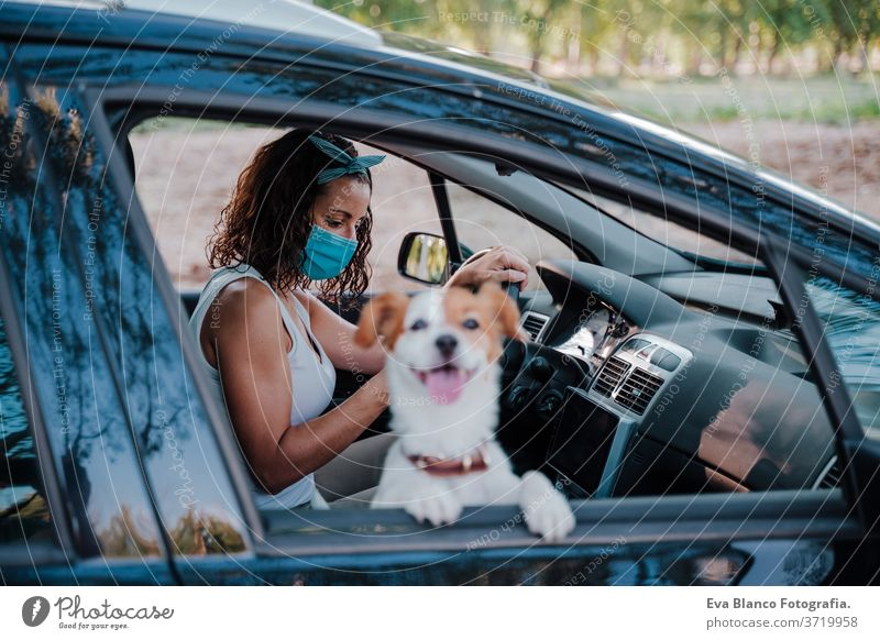 young woman wearing protective mask in a car. cute jack russell dog besides. Travel and new normal concept corona virus travel sun love driveway happy