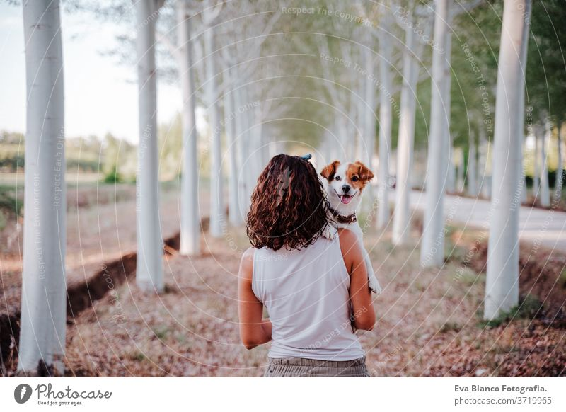 young happy woman in a car cuddling her cute dog. Travel concept sunset outdoors love together park jack russell lifestyle friendship vacation breed tender