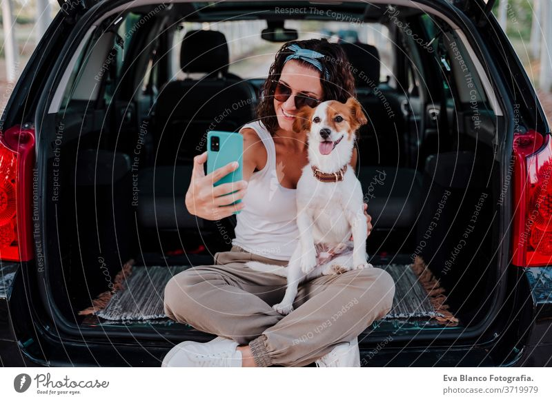 young happy woman in a car enjoying with her cute dog. Taking a selfie with mobile phone. Travel concept technology travel jack russell together love outdoors