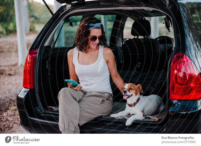 young happy woman in a car enjoying with her cute dog. Travel concept travel jack russell together love outdoors lifestyle friendship vacation animal breed