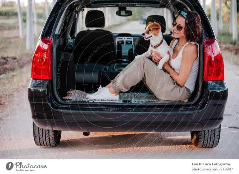 young happy woman in a car cuddling her cute dog. Travel concept travel jack russell together love outdoors lifestyle friendship vacation animal breed tender