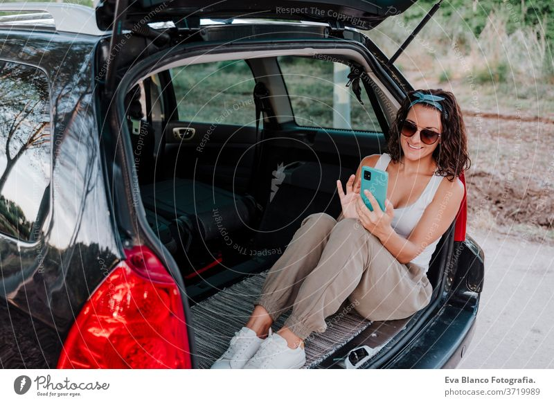 young happy woman in a car using mobile phone. Travel concept travel caucasian smiling outdoors waiting adult contraption communication lifestyle sitting